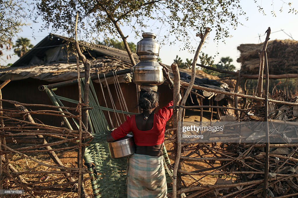 A woman carries a pot of water on her head in Kainad, Maharashtra, India, on Saturday, Dec. 21, 2013. The construction of 600,000 kilometers (373,000 miles) of country roads, addition of 327 million rural phone connections and a rise in literacy to record levels since Prime Minister Manmohan Singh took office in 2004 has helped double the growth rate of Indias food output. Photographer: Dhiraj Singh/Bloomberg via Getty Images