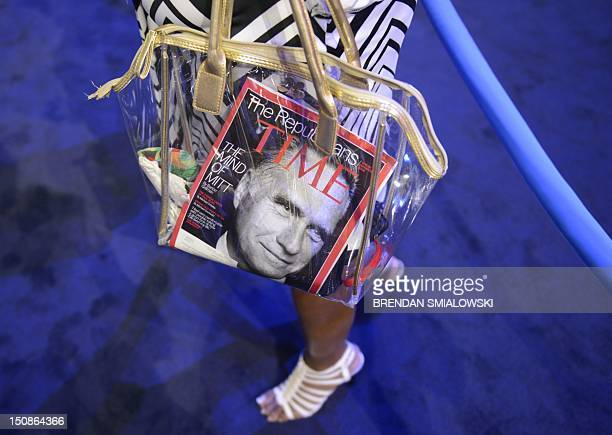 A woman carries a purse with a Time Magazine featuring Republican presidential candidate Mitt Romney on the cover at the Tampa Bay Times Forum in...