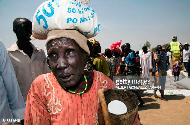 A woman carries a sack of food on March 4 in a stabilisation center in Ganyiel Panyijiar county in South Sudan South Sudan was declared the site of...