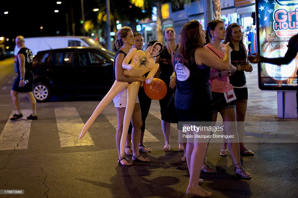 A woman carries a sex doll in the street around the British Square on August 9, 2013 in Benidorm, Spain. Benidorm is one of Europe's top package holiday destinations and one of Spain's busiest tourist destinations. The Costa Blanca hotspot of Benidorm is calculated to have a population of around 72,000, which is estimated to rise to more than 300,000, during the summer months as the tourists and visitors flock to its popular beaches.