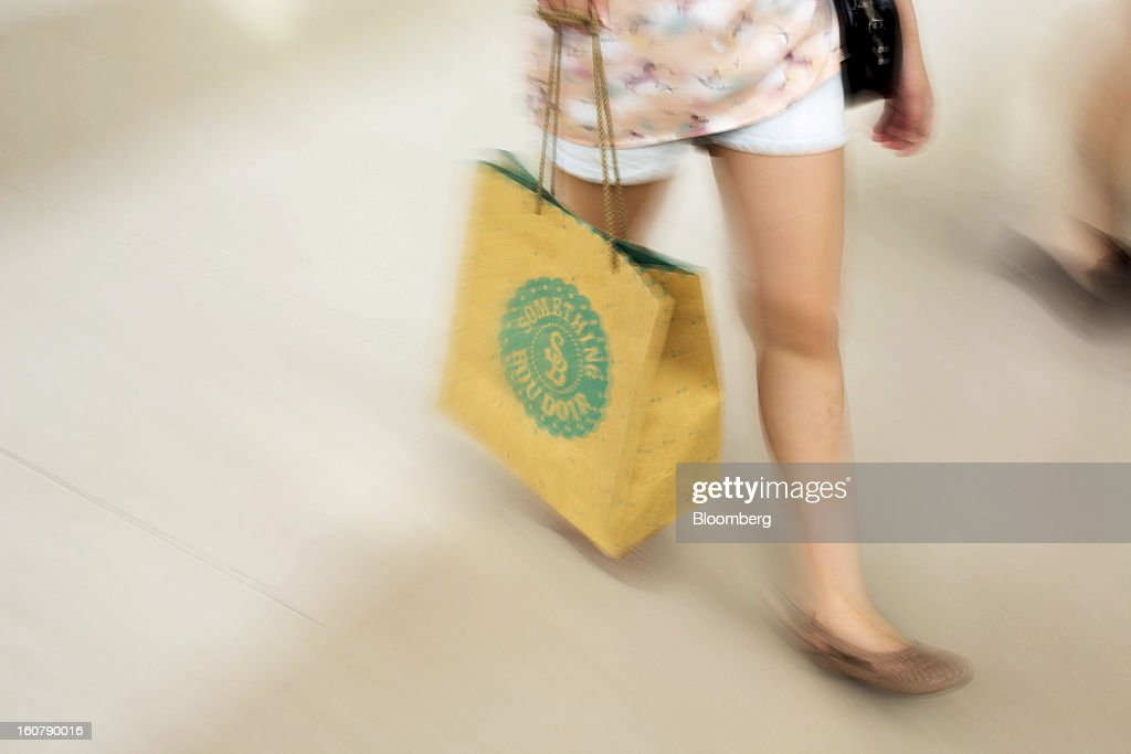 A woman carries a shopping bag as she walks through the Siam Paragon shopping mall in Bangkok, Thailand, on Tuesday, Feb. 5, 2013. Thai inflation may average 2.8 percent this year, the Bank of Thailand said. Photographer: Brent Lewin/Bloomberg via Getty Images