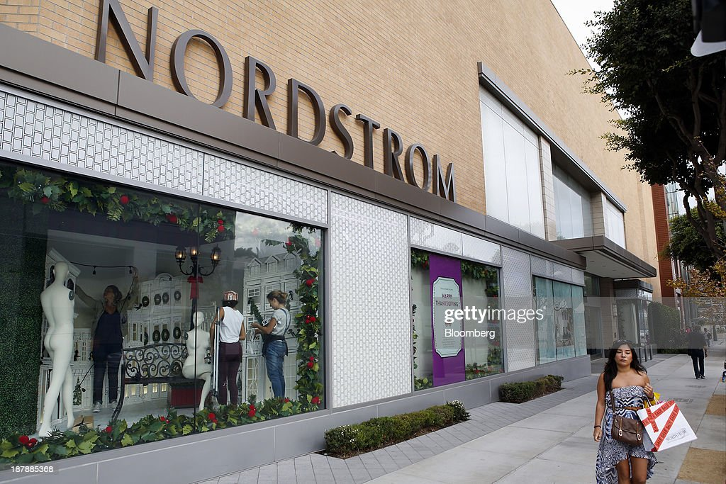 A woman carries a shopping bag while walking past a Nordstrom Inc. store in Santa Monica, California, U.S., on Tuesday, Nov. 12, 2013. Nordstrom Inc. is scheduled to release earnings figures on Nov. 14. Photographer: Patrick T. Fallon/Bloomberg via Getty Images