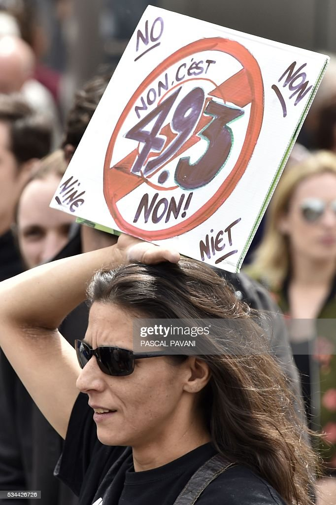 A woman carries a sign against the goverment's use of Article 49-3 of France's Constitution, permitting the passage of law by decreee, during a demonstration against proposed government labour and employment law reforms on May 26, 2016 in Toulouse. Workers at nuclear power stations in France were set to go on strike May 26, joining a growing protest movement against controversial labour market reforms that has already severely disrupted fuel supplies. Unions have called for fresh rallies in cities across France on May 26, the latest bout of social unrest that started around three months ago and has frequently turned violent. PAVANI