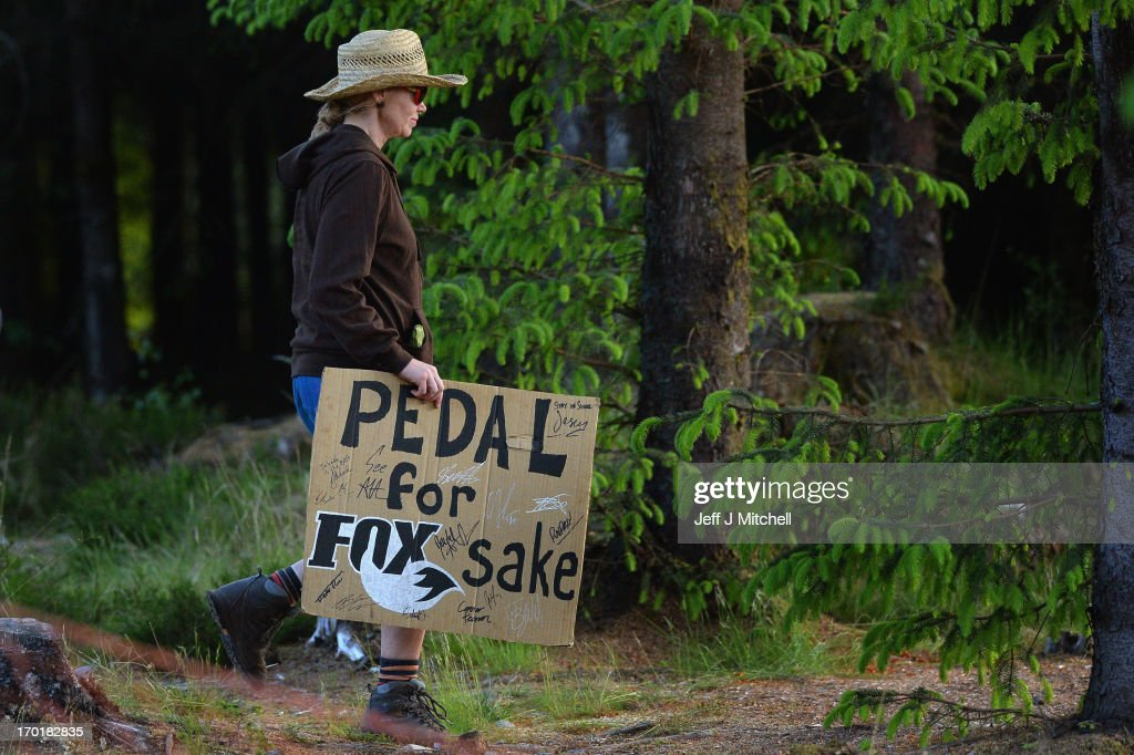 A woman carries a sign next to the course for the four cross pro tour qualification at the UCI Mountain Bike World Cup on June 8, 2013 in Fort William, Scotland.