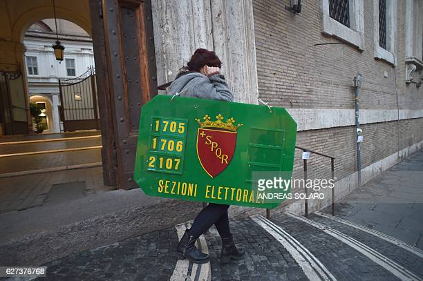 A woman carries a sign to hang at the entrance of a polling station on the eve of a crucial referendum on constitutional reforms on December 3 2016...