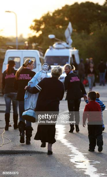 A woman carries a statue as she leaves Dale Farm near Basildon Essex the UK's largest illegal site after the end of a twoday stand off against...