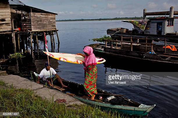 A woman carries a surf board as prepares during Bekudo Bono festival at Kampar river on November 19 2013 in Teluk Meranti village Riau Province...