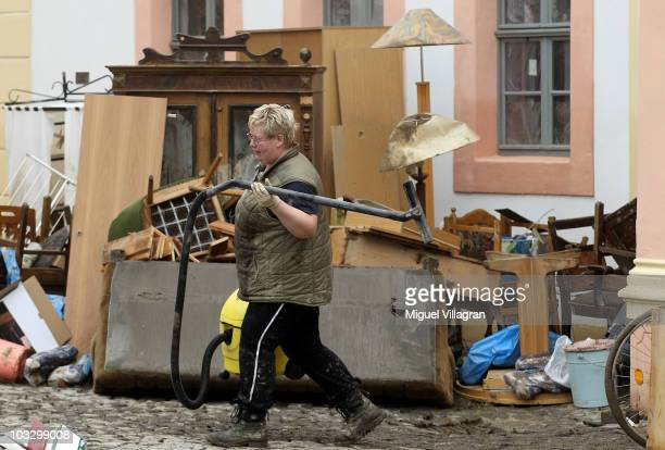 A woman carries a vacuum cleaner as she walks past destroyed furniture after the St Marienthal Cistercian convent was flooded on August 9 2010 in...