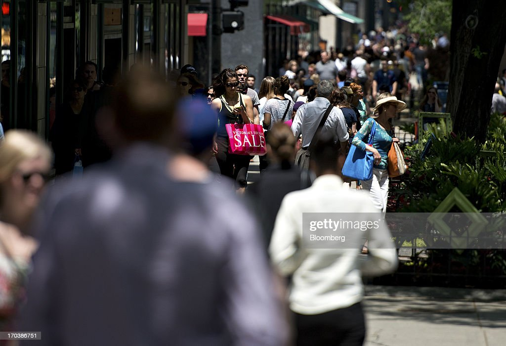 A woman carries a Victoria's Secret shopping bag, center, as she walks through a retail area known as the 'Magnificent Mile' in Chicago, Illinois, U.S., on Tuesday, June 11, 2013. Sales at U.S. retailers probably rose in May as an improving job market gave consumers the confidence to shop for automobiles, home furnishings and clothing, economists said before reports this week. Photographer: Daniel Acker/Bloomberg via Getty Images