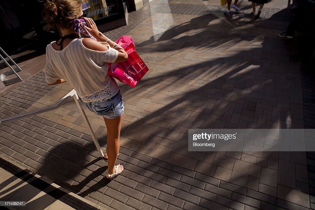 A woman carries a Victoria's Secret shopping bag while talking on the phone at the Fashion Valley Mall in San Diego, California, U.S., on Saturday, June 22, 2013. The Bureau of Economic Analysis is schedule to release personal consumption figures on June 26. Photographer: Sam Hodgson/Bloomberg via Getty Images