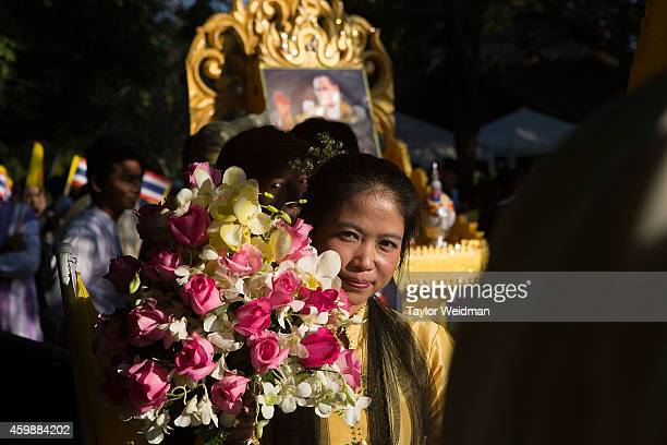 A woman carries an offering of flowers during a parade and ceremony in honor of the King's birthday on December 3 2014 in Chiang Mai Thailand...