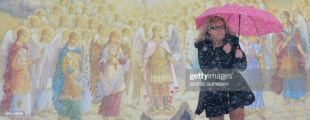 A woman carries an umbrella to protect herself from heavy snow fall as she walks in front of frescos of Mykhaylo Gold Domes Cathedral in Kiev on January 31, 2013.