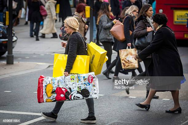 A woman carries bags of shopping on Oxford Street during 'Black Friday' sales on November 28 2014 in London England Originating in the USA as a sales...