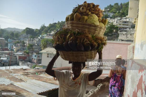 A woman carries baskets with vegetables on her head in the streets of Jalousie neighborhood in the commune of Petion Ville PortauPrince on June 20...