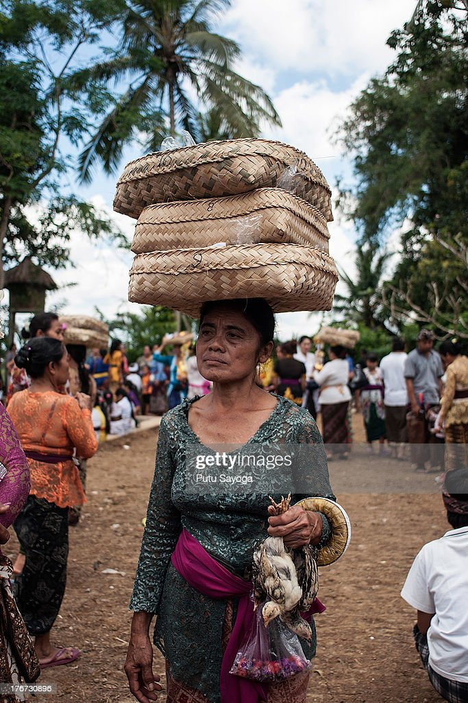 A woman carries birds to the cremation site as an offering during a Balinese Hindu mass cremation on August 18, 2013 in Ubud, Bali, Indonesia. More than 60 corpses were collectively cremated to share the expense of the ceremony. Well known as Ngaben, it is one of the most important ceremonies for Balinese Hindu people, as they believe it will free the spirit from the deceased body so it can reincarnate.