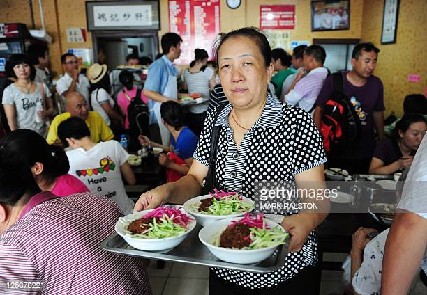 A woman carries bowls of 'Pork Noodles in Brown Bean Sauce' in the crowded the Yaoji Chaogan restaurant after the restaurant's popularity soared due...
