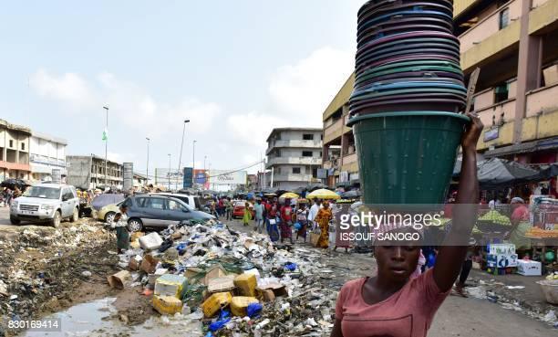 A woman carries buckets as she walks past a trash heap at the market of Adjame a working class neighbourhood of Abidjan on August 10 2017 / AFP PHOTO...