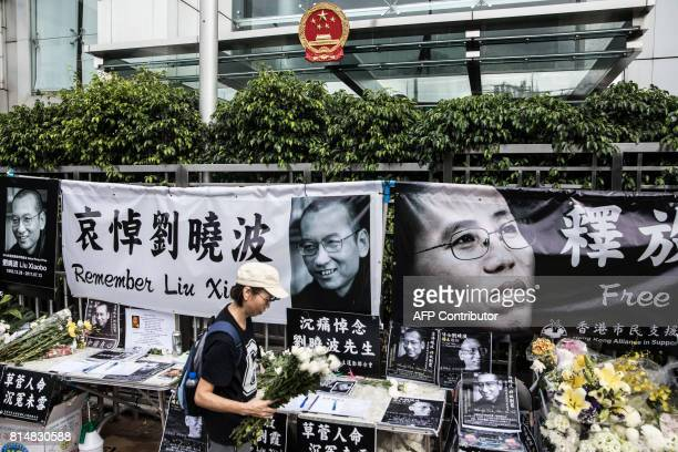 A woman carries flowers at a makeshift memorial for the late Chinese Nobel laureate Liu Xiaobo outside the Chinese Liaison Office in Hong Kong on...