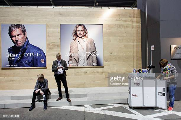 A woman carries food carts drinks while Participant sitting below advertising poster at the Marc O'Polo brand stand at the Bread and Butter trade...