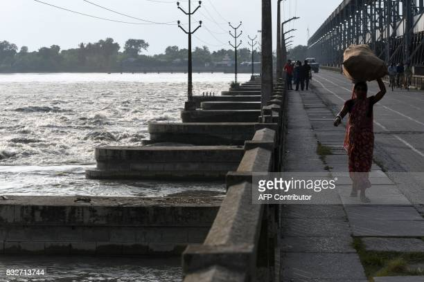 A woman carries goods on her head as she crossed Koshi Barrage a flood control sluice across the Koshi River Birpur Sunsari district some 250 kms...