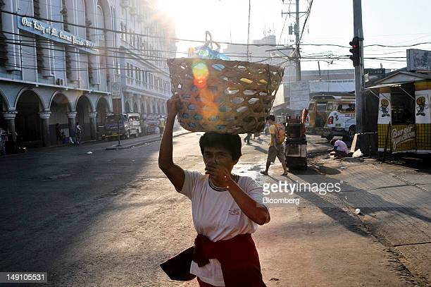 A woman carries goods on her head as she leaves a market in Cebu the Philippines on Wednesday June 20 2012 Standard Poor's this month raised the...
