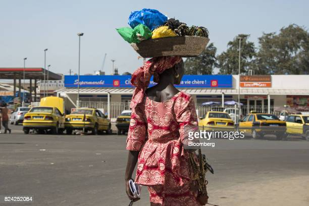 A woman carries goods on her head in front of a Citydia supermarket store in Dakar Senegal on Friday July 28 2017 Senegalese voters will elect a new...
