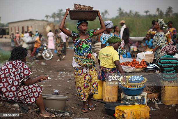 A woman carries goods while unloading her boat of produce at a market on January 6 2012 in Ganvie near Cotonou Benin Often called the Venice of...