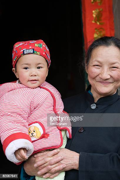 Woman carries granddaughter in Fuli Xingping China has a one child family planning policy to limit population