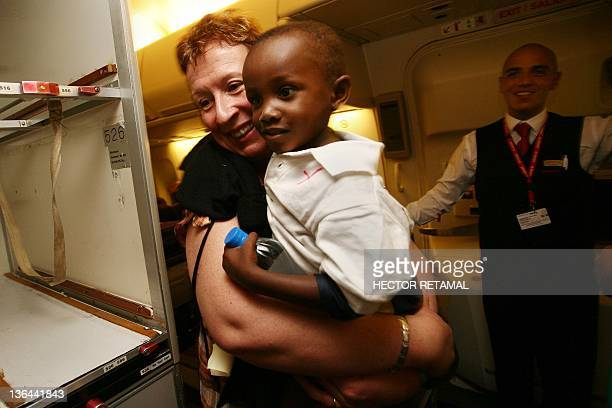 A woman carries her adopted Haitian child aboard an airplane before departing for France at PortauPrince's Toussaint Louverture airport on December...
