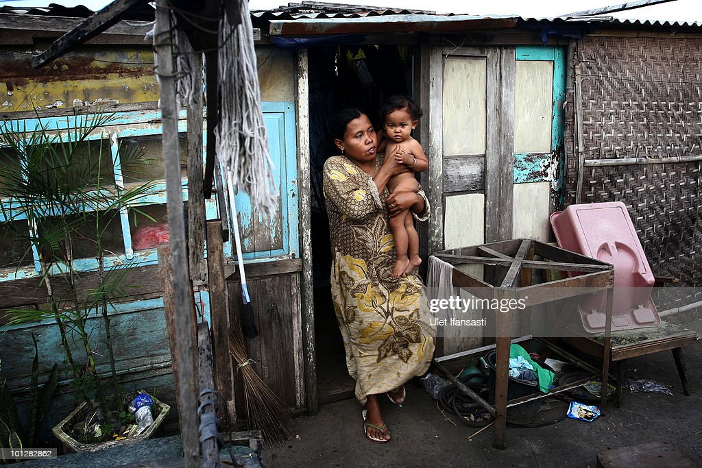 A woman carries her baby in their temporary house whose house was submerged by mud from the mud volcano 'Lusi' on May 30, 2010 in the subdistrict of Porong in Sidoarjo, East Java, Indonesia. Mud and gases continue to spew from Lusi four years after it first erupted, suspected to be triggered by the drilling activities of Indonesian oil and gas exploration company Lapindo Brantas. The initial eruption engulfed entire communities, wiping out villages and killing 13 people. Mud flow from the volcano continues at a rate of up to 150,000m3 per day, and to date has displaced tens of thousands of people.