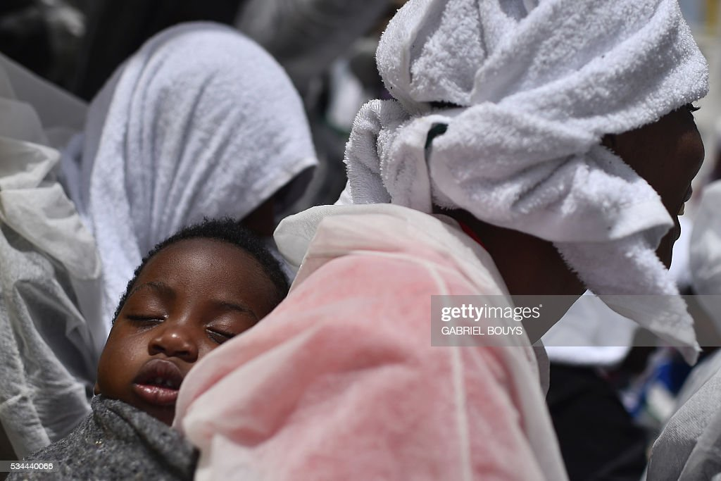 A woman carries her baby on her back prior to leave rescue ship 'Aquarius' as more than 380 migrants arrive in the port of Cagliari, Sardinia, on May 26, 2016, two days after being rescued near the Libyan coasts. The Aquarius is a former North Atlantic fisheries protection ship now used by humanitarians SOS Mediterranee and Medecins Sans Frontieres (Doctors without Borders) which patrols to rescue migrants and refugees trying to reach Europe crossing the Mediterranean sea aboard rubber boats or old fishing boat. / AFP / GABRIEL