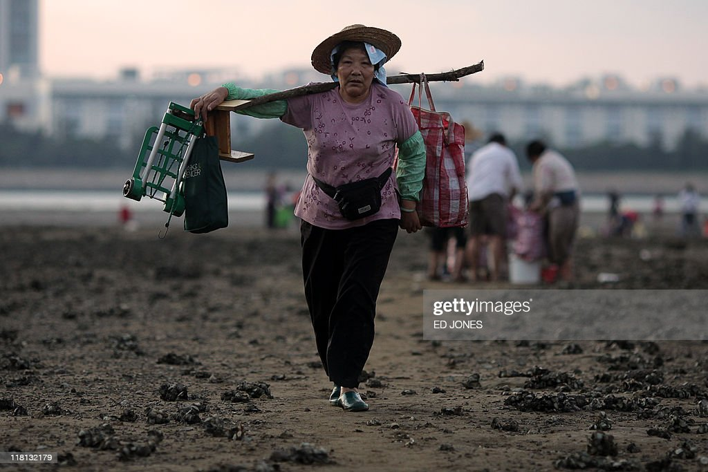 A woman carries her catch of clams from the rising tide on Lantau island, Hong Kong on July 3, 2011. Whether for business or pleasure, the tradition of digging for clams is a regular draw for residents of Hong Kong's outlying islands. Bounty hunters prepared to spend hours hunched over barnacled rocks can expect a sure reward for their currency of clams from the ever-present nearby seafood establisments only too happy to serve up a hard-won catch.