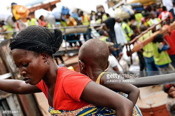 A woman carries her child as people from the Democratic Republic of Congo arrive on an ATC boat from neighboring Congo Brazzaville after being...