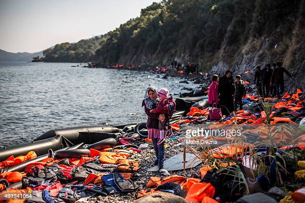 A woman carries her child as she arrives with other refugees on the shores of the Greek island of Lesbos after crossing the Aegean sea from Turkey on...