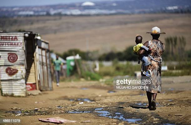A woman carries her child as she walks alongside a line of shacks in the impoverished township of Diepsloot on the outskirts of Centurion on April 24...
