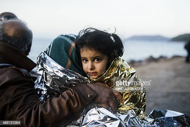 A woman carries her child wrapped in an emergency blanket shortly after arriving with other migrants and refugees on the Greek island of Lesbos after...