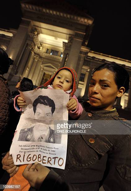 A woman carries her daughter and a poster with the picture of her missing father during a rally staged by survivors and relatives of victims of...