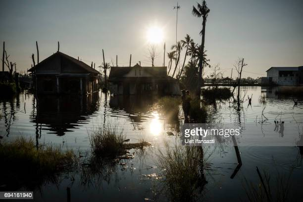 A woman carries her daughter walk through flood caused by rising sea levels on June 6 2017 in Pekalongan Indonesia Indonesia is known to be one of...