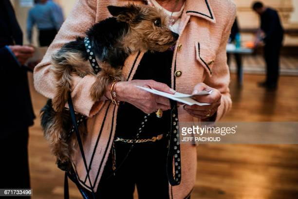 A woman carries her dog as she cast her ballot at a polling station in Lyon on April 23 during the first round of the Presidential elections / AFP...