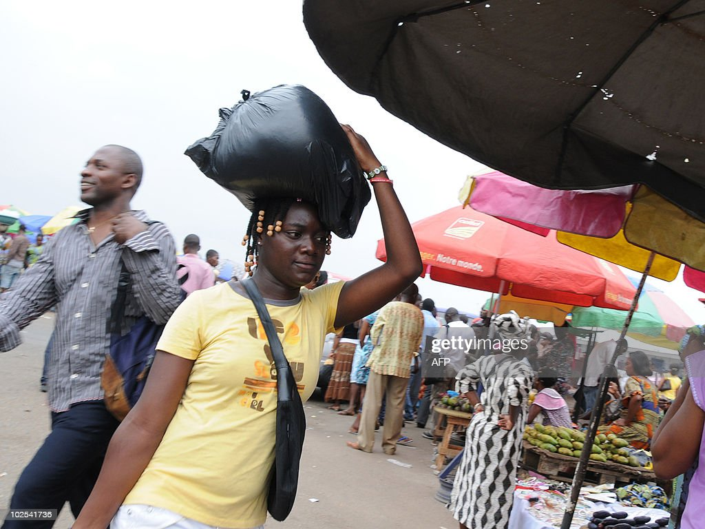 A woman carries her plastic shopping bag on her head in a market in Libreville on June 29 2010 'It is a revolution in consummerism' affirms Pepecy...