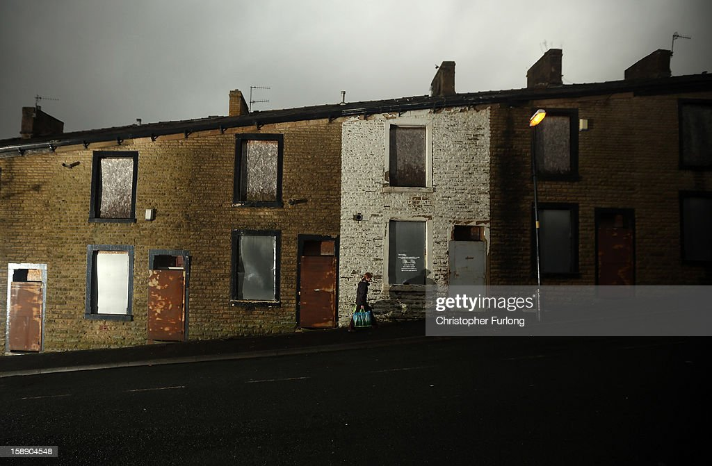 A woman carries her shopping past empty former council houses that line a street, in the Lancashire town of Accrington, which are waiting to be modernised by private developers on January 3, 2013 in Accrington, England. There are estimated to be 850,000 empty homes in the United Kingdom even though local councils still have long waiting lists for housing. The terraced houses were due to be rejuvenated by Accrington council but the project was put on hold when the government cut a housing regeneration project.