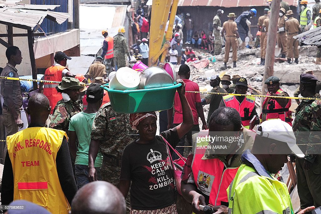 A woman carries his belongings as dhe evacuates on May 3, 2016 the rubble of the six-storey building that collapsed killing 23 people in Nairobi's suburb of Huruma. Kenyan rescuers pulled an 18-month-old toddler alive from the rubble of a six-storey building on May 3, four days after the block collapsed killing 23 people, police said. Located in the poor, tightly-packed Huruma neighbourhood, the building had been slated for demolition after being declared structurally unsound. But an evacuation order for the structure, which was built near a river just two years ago, was ignored. MAINA