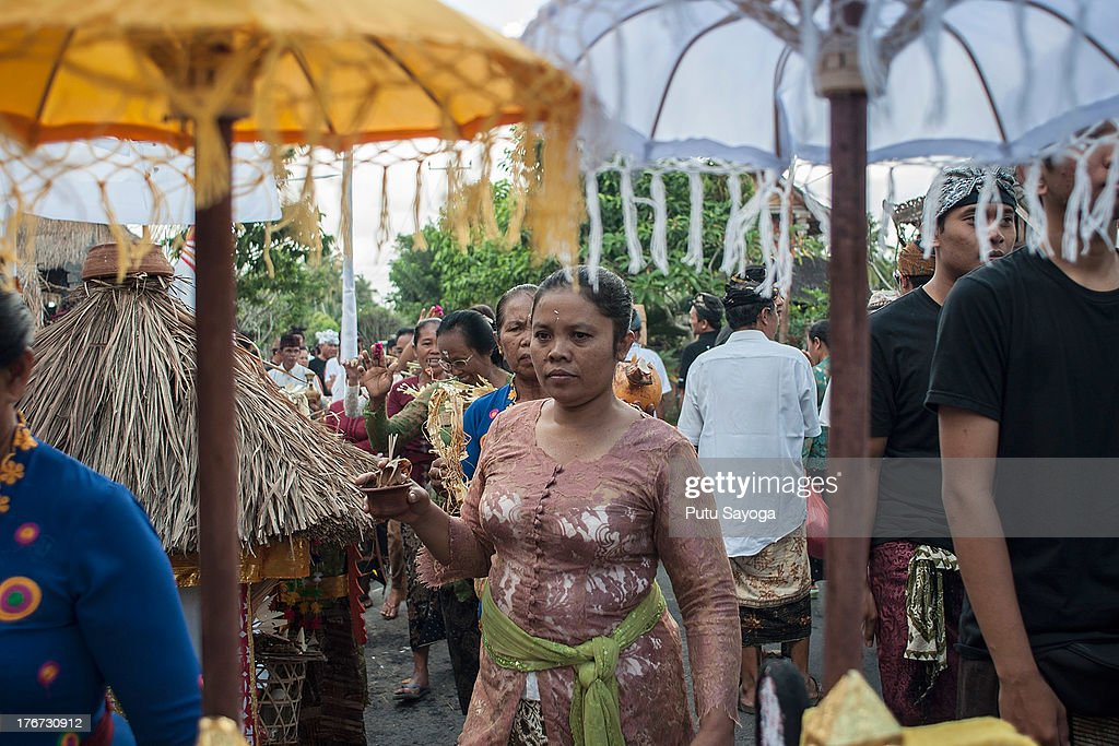 A woman carries holy water during a Balinese Hindu mass cremation on August 18, 2013 in Ubud, Bali, Indonesia. More than 60 corpses were collectively cremated to share the expense of the ceremony. Well known as Ngaben, it is one of the most important ceremonies for Balinese Hindu people, as they believe it will free the spirit from the deceased body so it can reincarnate.