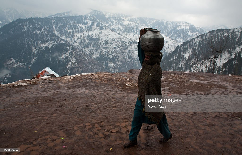 A woman carries metal pitcher filled with water on her head in Churunda village on January 12, 2013, northwest of Srinagar, the summer capital of Indian Administered Kashshmir, India. The village with a population of a little over 12,000 people has been bearing the brunt of cross-fire between nuclear rivals India and Pakistan. Last week a Pakistan solider was killed across the Line of Control (LOC), a military line that divides Indian-administered Kashmir from the Pakistan-administered Kashmir at this village. People living along the LoC have continually been at risk due to hostility between the armies of the two rival nations. Last year, in November, three people, including a pregnant woman, had died after a shell fired from Pakistan landed on one of the houses in the village. Tension between Pakistan and India has escalated after a fresh skimirish along the border. Both countries have summoned each other's envoy to protest against unacceptable and unprovoked' attacks.