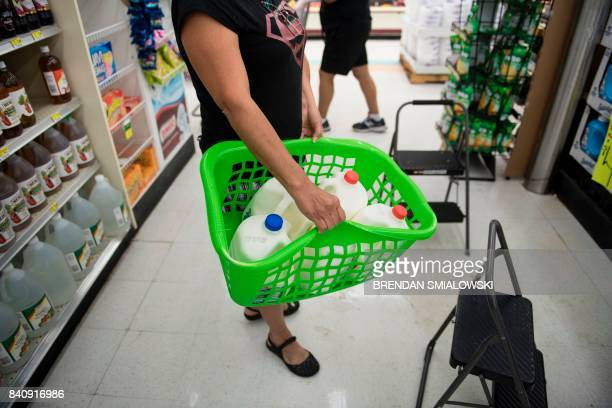 A woman carries milk in a laundry basket at the Food Town grocery store during the aftermath of Hurricane Harvey on August 30 2017 in Houston Texas...