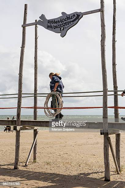 Woman carries rope over wooden quay