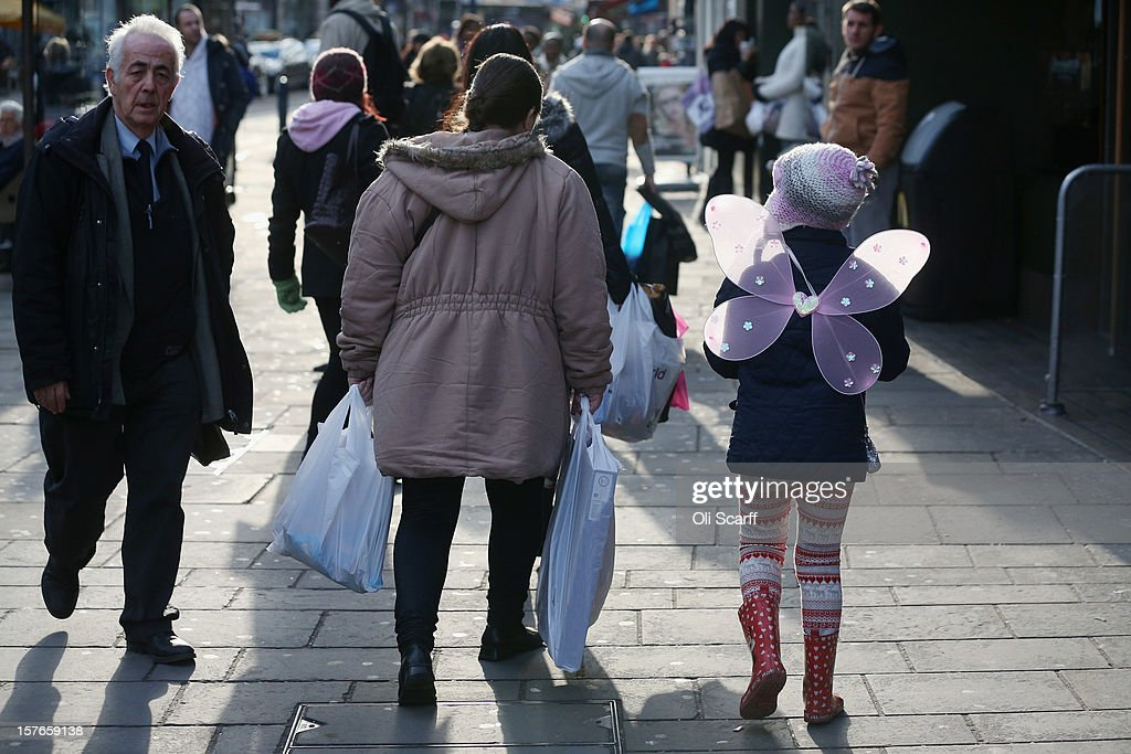 A woman carries several shopping bags along Lewisham high street on December 5, 2012 in London, England. The Chancellor of the Exchequer George Osborne has stated that the United Kingdom's economy is still struggling during his autumn budget statement to Parliament.