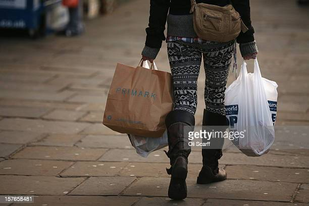 A woman carries several shopping bags from discount shops along Lewisham high street on December 5 2012 in London England The Chancellor of the...
