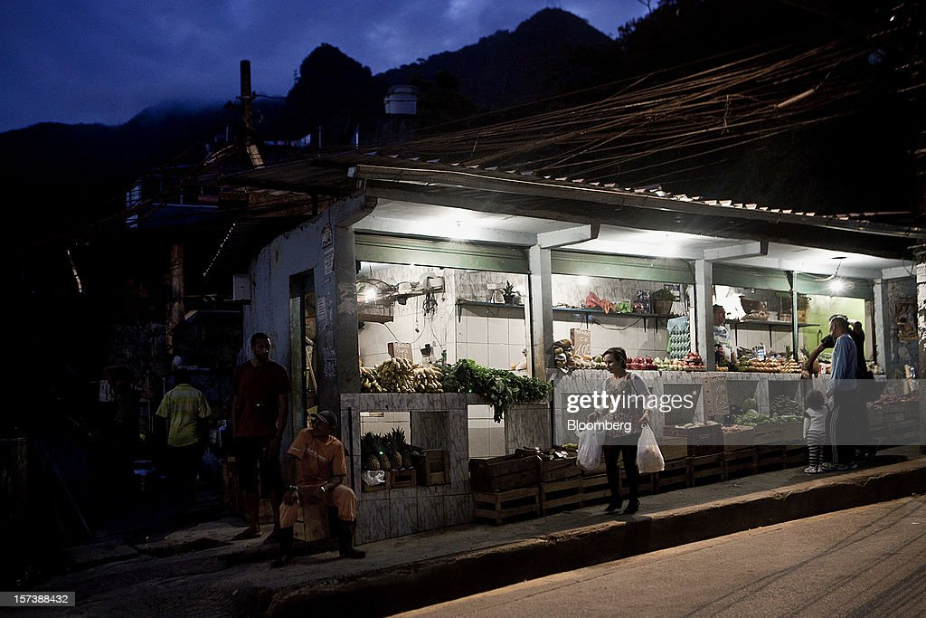 A woman carries shopping bags after making purchases at a fruit and vegetable stand in the Rocinha slum of Rio de Janeiro, Brazil, on Wednesday, Nov. 28, 2012. About 56 percent of the 12 million people who live in slums like Rocinha were considered middle class in 2011, up from 29 percent in 2001, according to a study this year by Instituto Data Popular, a Sao Paulo-based research group. Photographer: Dado Galdieri/Bloomberg via Getty Images