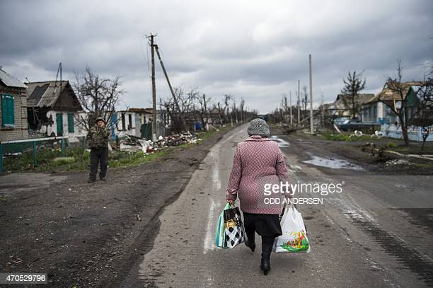 A woman carries shopping bags as she walks back to the village of Nikishino on April 21 2015 in the selfproclaimed Donetsk People's Republic Only a...